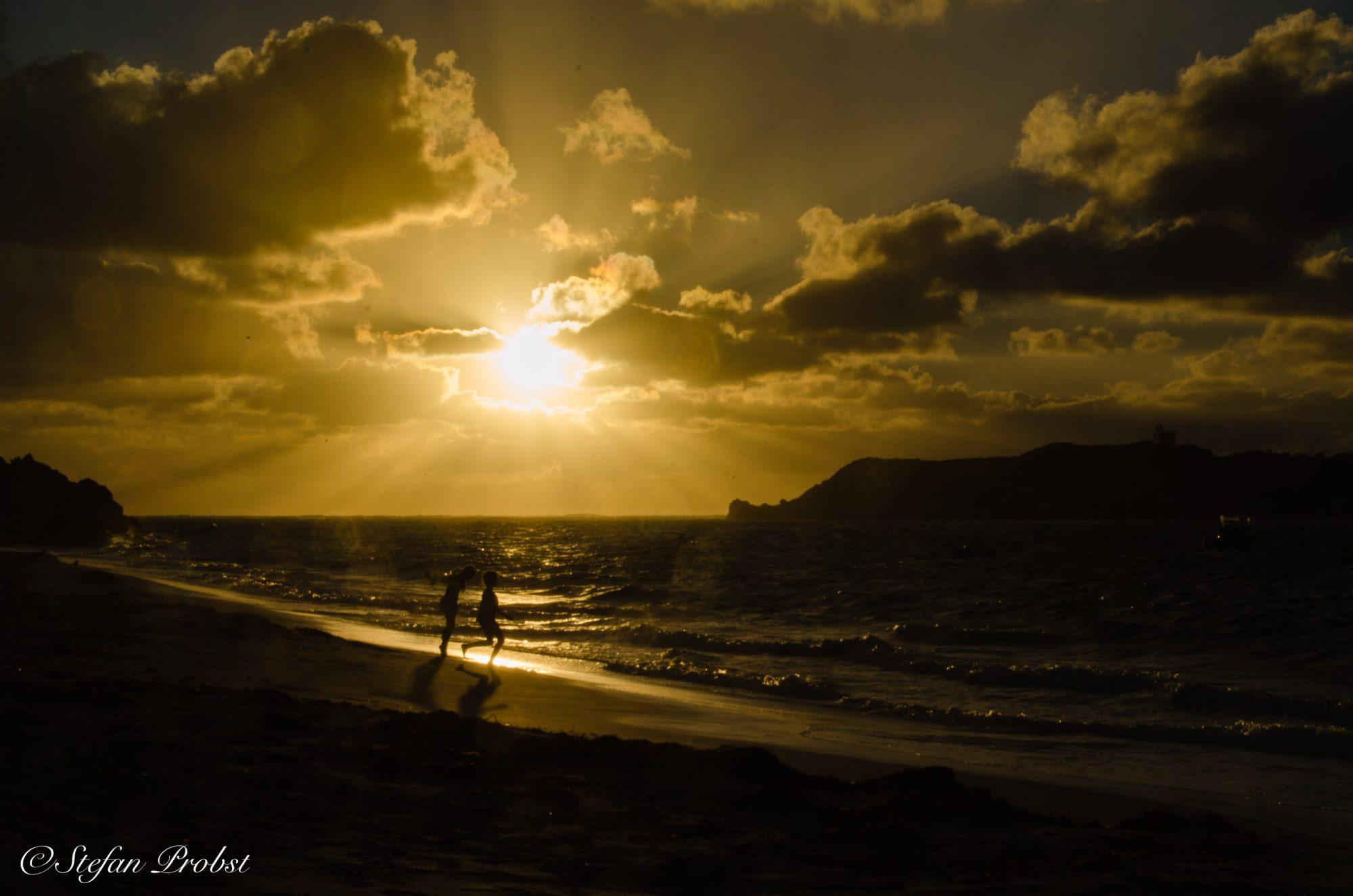 Im Sonnenuntergang spielende Kinder am Strand der Hamelin Bay
