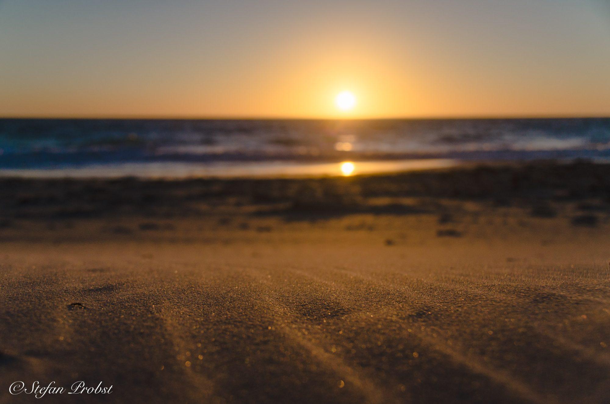 Wellen im Sand bei Sonnenuntergang
